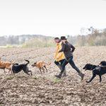 Julie Willems courant dans les champs avec les chiens